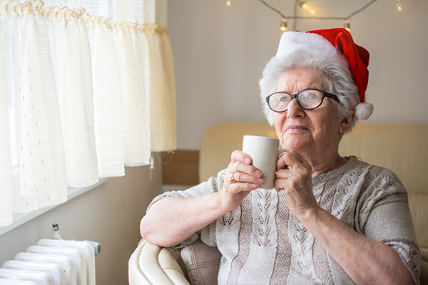 Senior woman with red Santa's hat holding hot tea and looking through window. Xmas, home, age, alone, senior concept.