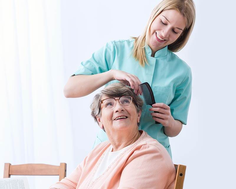 Caregiver brushing client's hair