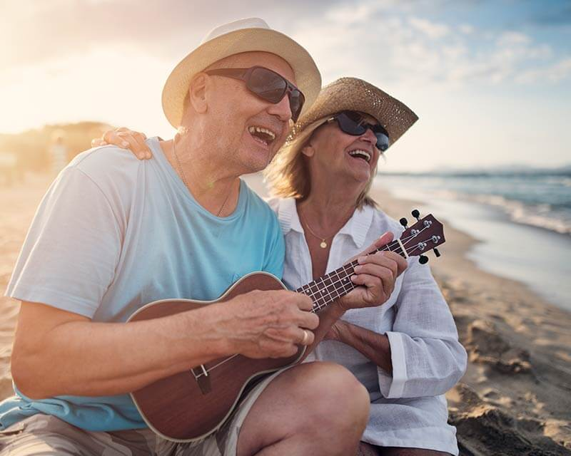 Retired couple enjoying the beach, singing and playing music