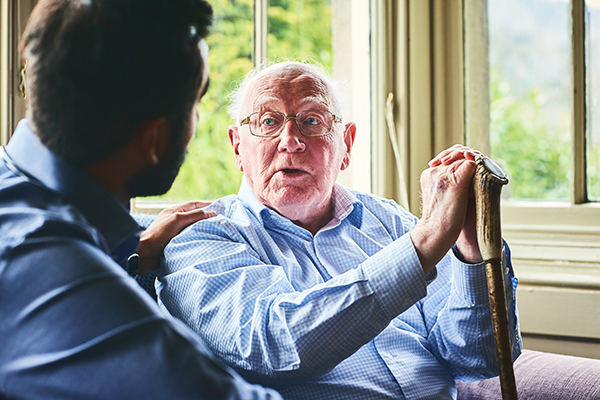 Elderly man talking with doctor at home