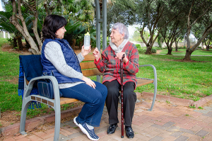 Female caregiver offers to drink to the older woman