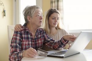 Senior woman with daughter online purchasing together