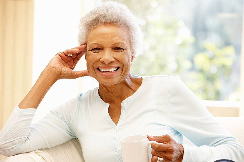senior woman at home drinking hot drink and smiling at the camera