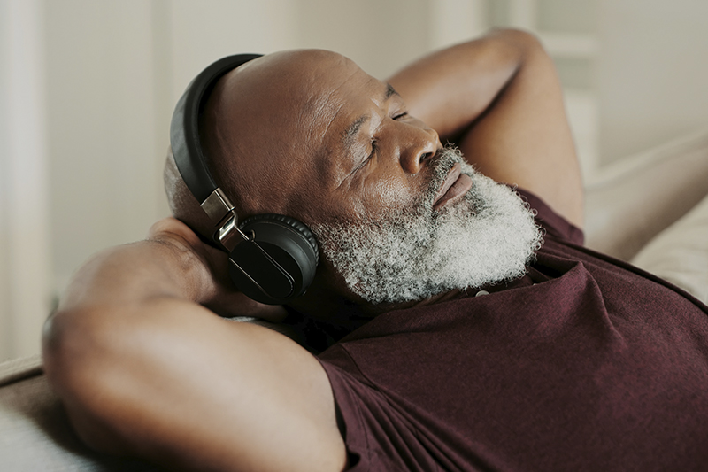 senior man resting and listening to headphones