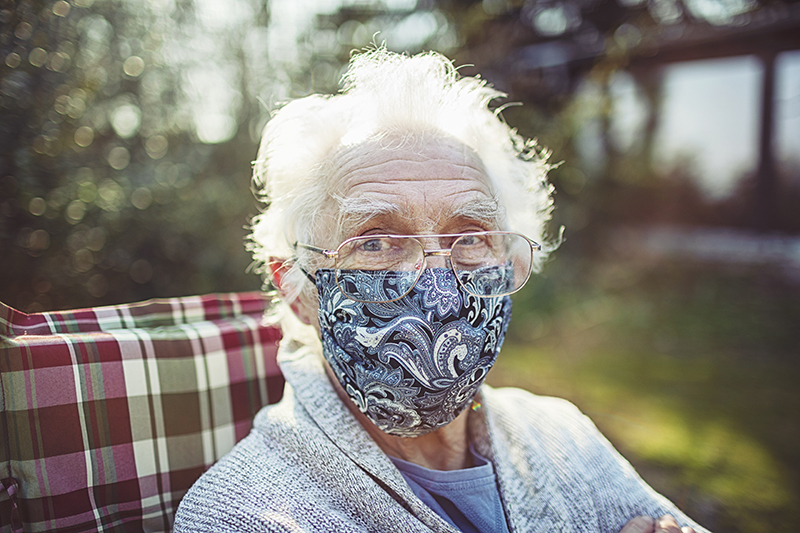 Friendly old senior wears a mask to protect against viruses and bacteria