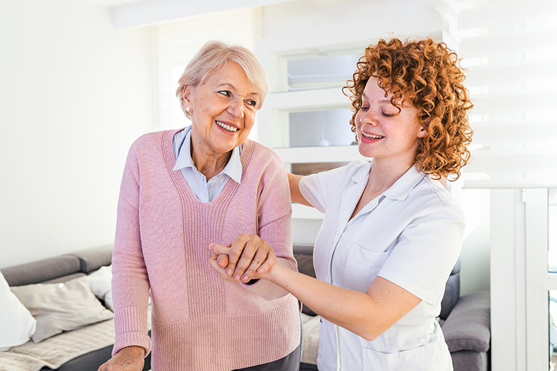 Smiling nurse helping senior lady to walk around the nursing home. Portrait of happy female caregiver and senior woman walking together at home. Professional caregiver taking care of elderly woman