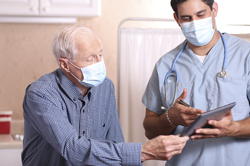 masked senior man talking with health professional