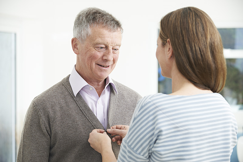 Adult Daughter Helping Senior Man To Button Cardigan
