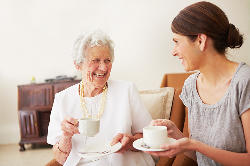 elderly lady having tea with her daughter